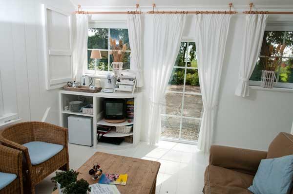 uitzicht naar de achtertuin en weide vanuit de zitkamer met veel ramen en witte gordijnen